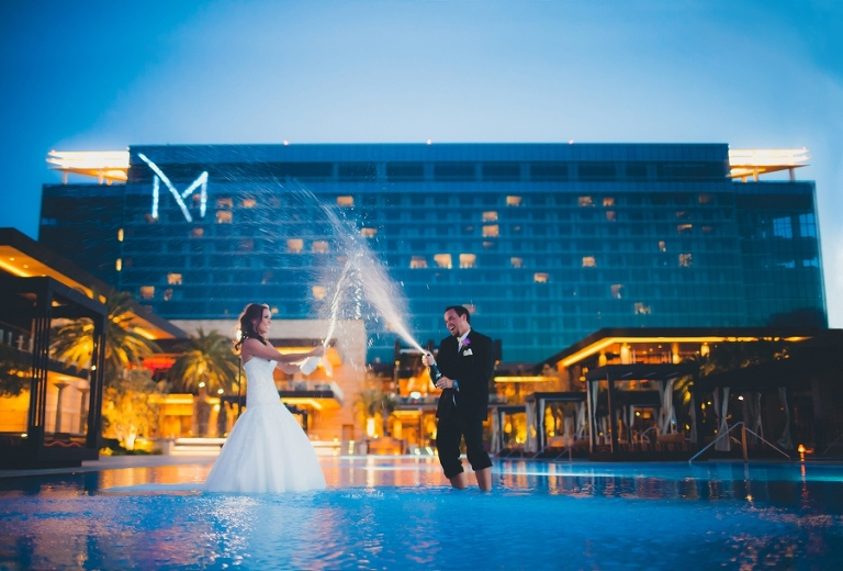 The M Resort wedding trash the dress photographer. Bride and groom popping champagne in pool at the M Resort.